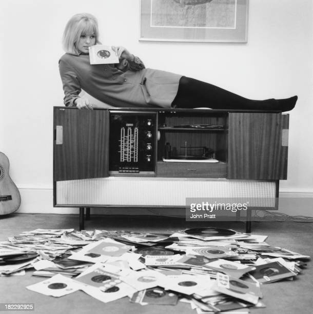 Disc jockey and presenter of the Rediffusion TV music show 'That's For Me' Anne Nightingale reclining on her stereogram at her home in Brighton...