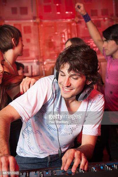 Disc jockey in nightclub with people dancing around him smiling
