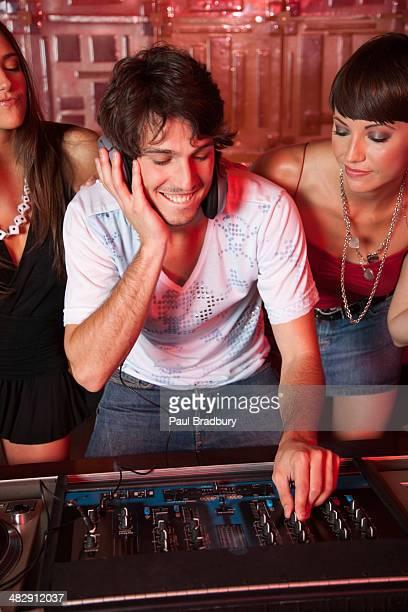 Disc jockey in nightclub with two women  behind him smiling