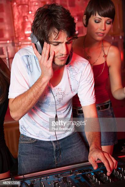 Disc jockey in nightclub with woman behind him