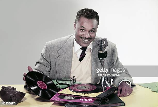 Disc jockey Joey Adams poses with vinyl records and a microphone in front of him ca1950s United States