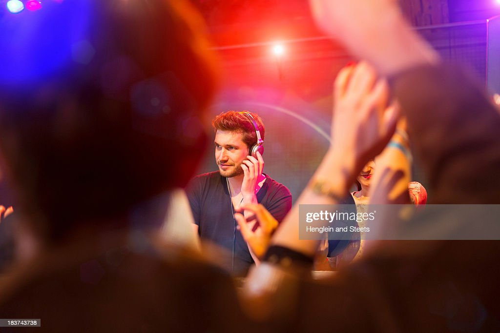 Disc jockey surrounded by people dancing : Stock Photo