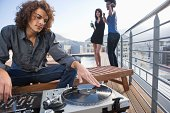 Disc jockey with turntable at party