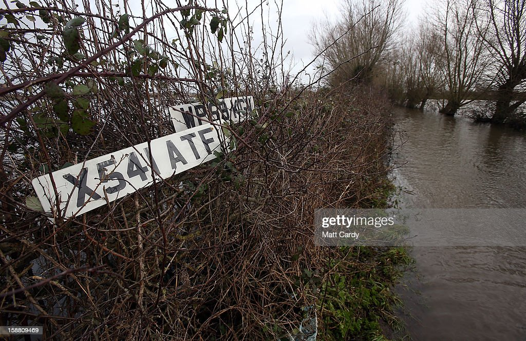 Discarded car registration plates are seen in a hedge beside flood waters surrounding the village of Muchelney, which has been cut off by flooding on the Somerset Levels, on December 30, 2012 near Langport, England. The Met Office is warning of the risk of further flooding towards the end of the year, meaning 2012 is set to be the wettest on record.