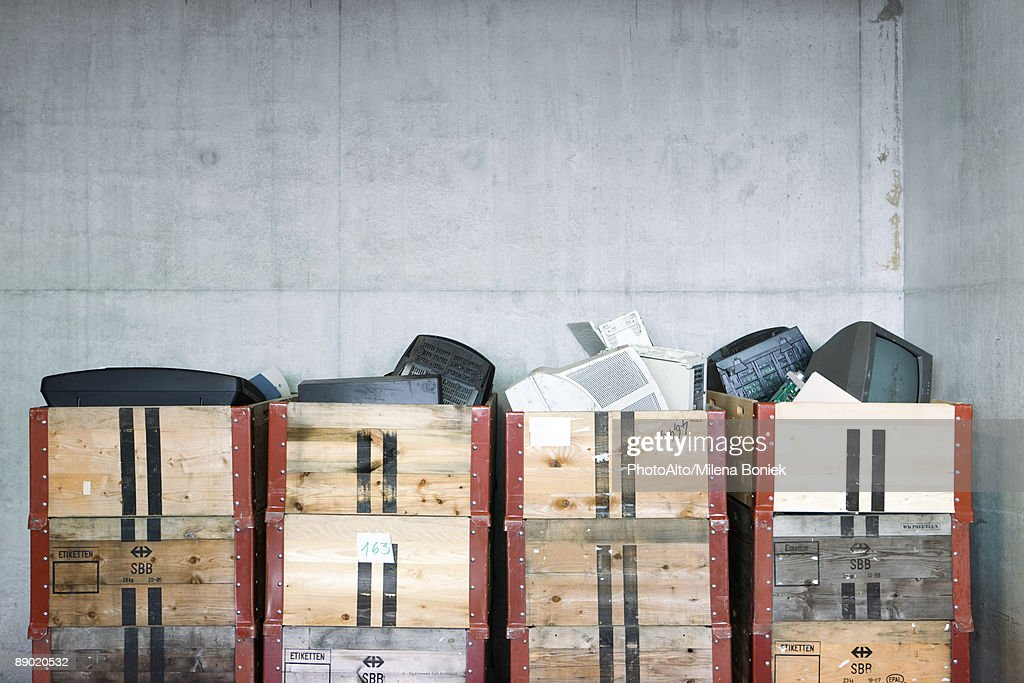 Discarded electronics in crates stacked in recycling center : Stock Photo