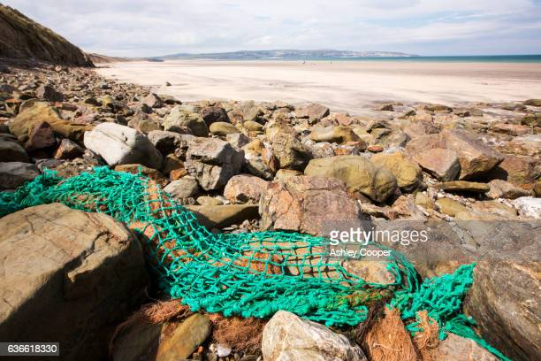 Discarded fishing net washed ashore on the beach at Gwithian Towans, a nature reserve on the Cornish coast near St Ives.