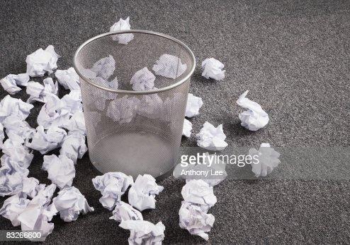 Discarded paper on floor around wastebasket : Stock Photo