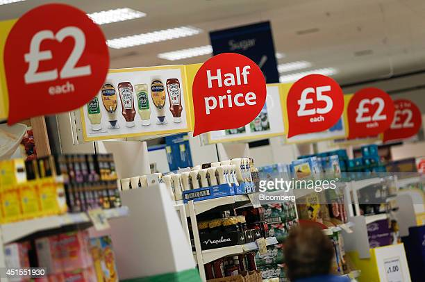 Discount and halfprice signs sit above goods displayed for sale on the end of aisles inside a Tesco Extra Supermarket operated by Tesco Plc in London...