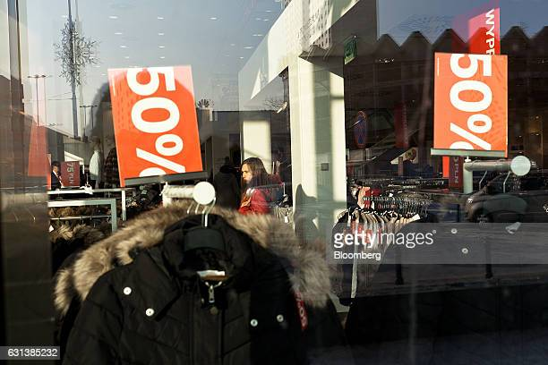 Discount signs sit on fashion rails inside an Hennes Mauritz AB store in central Warsaw Poland on Monday Jan 9 2017 Investors in Poland are betting...