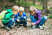 Kids with magnifying glasses exploring the nature. Slightly soft.