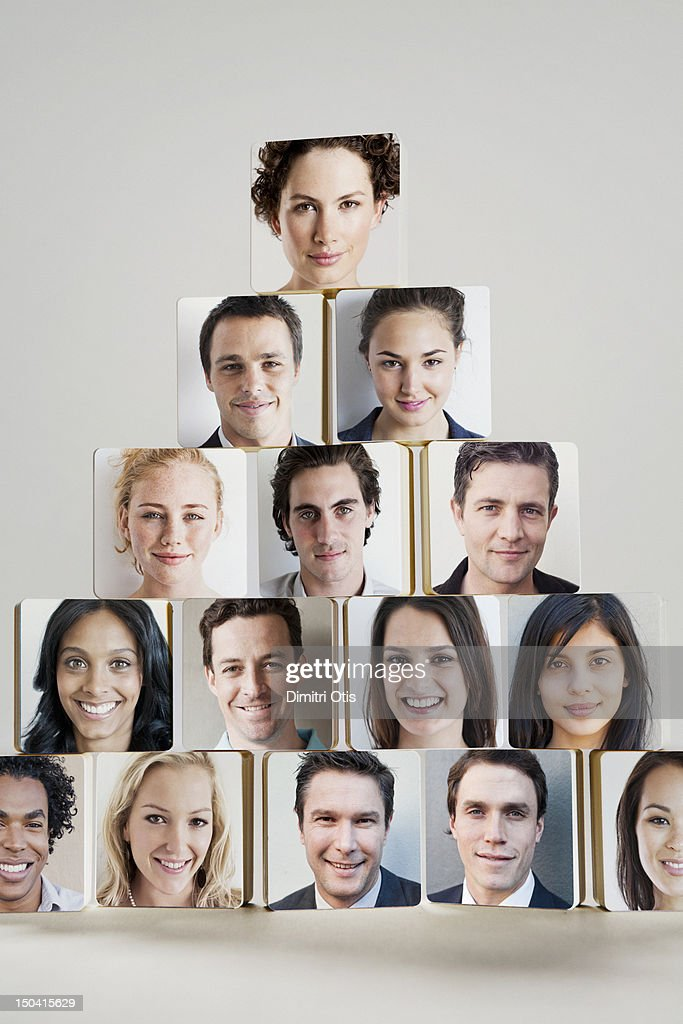 Disc's with faces in pyramid pile, woman at head : Stock Photo