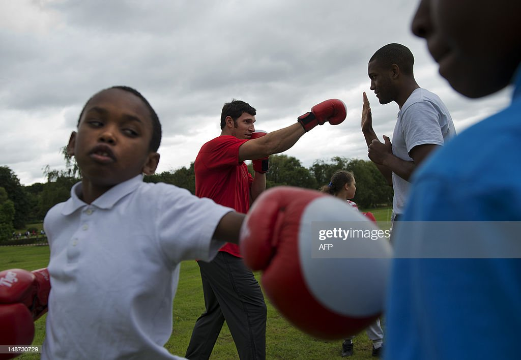 US discus thrower Lance Brooks (C) practices boxing with an instructor alongside schoolchildren during a visit to a recreation ground beside Alexander Stadium, the Team USA track and field training camp, in Birmingham on July 19, 2012. Brooks competes in the discus and is the Olympic Trials Champion.