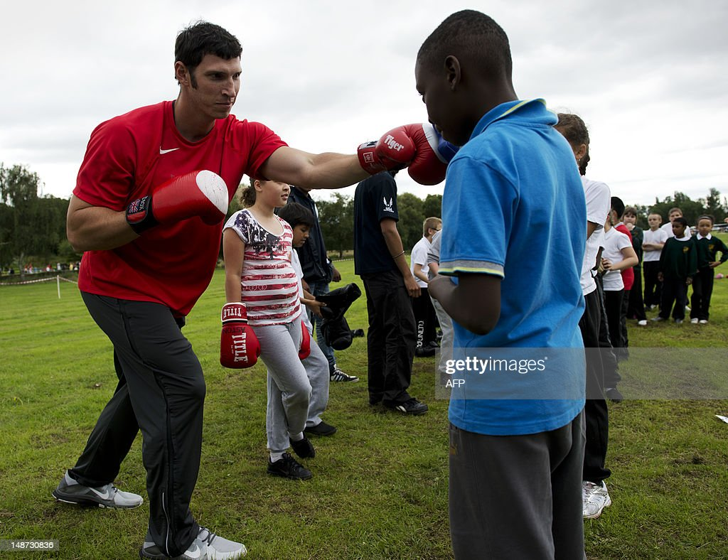 US discus thrower Lance Brooks (L) practices boxing with an instructor alongside schoolchildren during a visit to a recreation ground beside Alexander Stadium, the Team USA track and field training camp, in Birmingham on July 19, 2012. Brooks competes in the discus and is the Olympic Trials Champion. AFP PHOTO / ADRIAN DENNIS