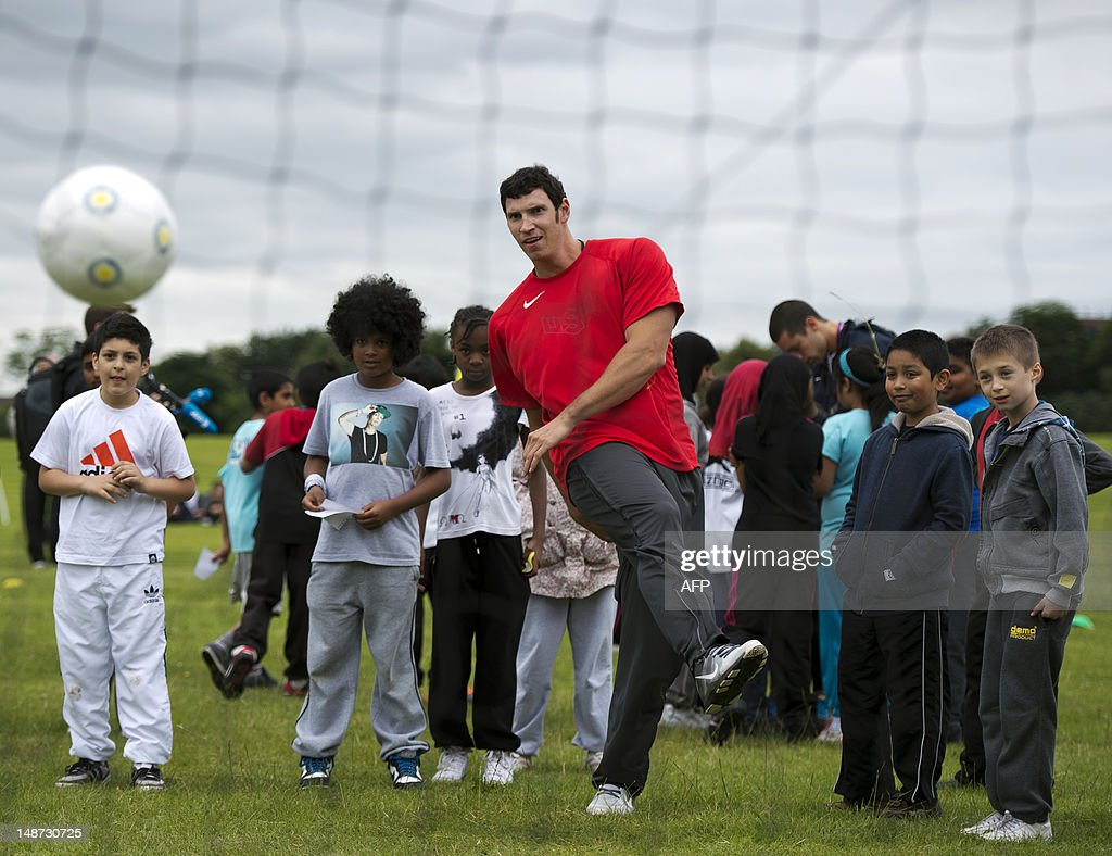 US discus thrower Lance Brooks (C) takes a shot at goal during football training with schoolchildren during a visit to a recreation ground beside Alexander Stadium, the Team USA track and field training camp, in Birmingham on July 19, 2012. Brooks competes in the discus and is the Olympic Trials Champion.