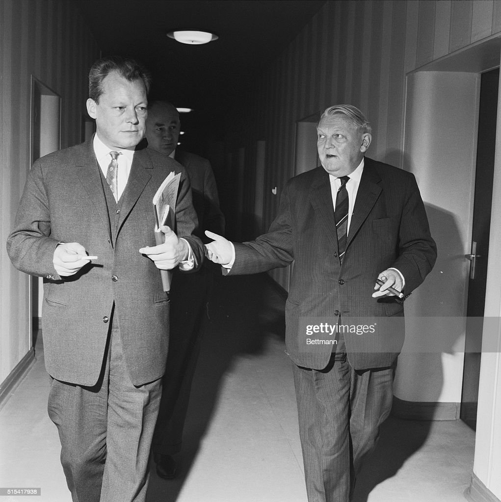 Discuss Aid for Berlin. Bonn, West Germany: Still apparently engrossed in their discussions, West Berlin mayor <a gi-track='captionPersonalityLinkClicked' href=/galleries/search?phrase=Willy+Brandt&family=editorial&specificpeople=94253 ng-click='$event.stopPropagation()'>Willy Brandt</a> (left) and West German Economics Minister <a gi-track='captionPersonalityLinkClicked' href=/galleries/search?phrase=Ludwig+Erhard&family=editorial&specificpeople=210784 ng-click='$event.stopPropagation()'>Ludwig Erhard</a> walk through hall in the Economics Ministry here. The West German government declared itself ready to assist the city of West Berlin with 500,000,000 D-Marks ($125 million) to over some the economic difficulties brought about by the East German measures of August 13th and thereafter.