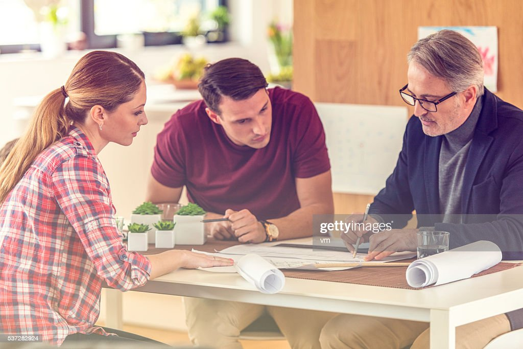 Discussing a blueprint : Stock Photo