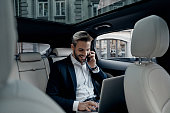 Handsome young man in full suit talking on smart phone and smiling while sitting in the car