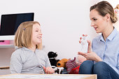 Child counselor discussing drawing with smiling girl during play therapy