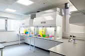 A white empty clinical room ready for use.  Well lit medical scientific laboratory with clear worktops and shelving space. No people. Scientific equipment, test-tubes, bottle, chemicals all behind a p