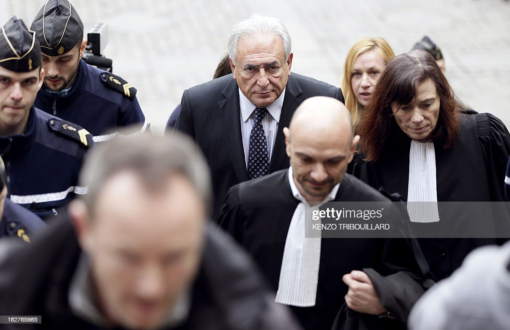 Disgraced former IMF chief Dominique Strauss-Kahn (C) arrives at Paris' courthouse after attending a hearing regarding his seizure request of the new book by Argentinian-born Marcela Iacub detailing their liaison, on February 26, 2013. Strauss-Kahn, who has called the book an 'abomination', is seeking 100,000 euros ($132,300) in damages and compensation from Iacub and her publisher Stock, and a similar amount from Le Nouvel Observateur, a magazine that published excerpts of the book.