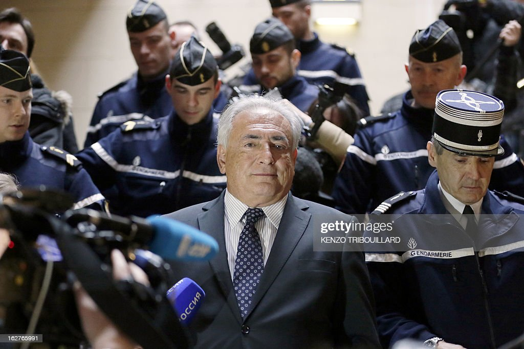Disgraced former IMF chief Dominique Strauss-Kahn (C) leaves Paris' courthouse after attending a hearing regarding his seizure request of the new book by Argentinian-born Marcela Iacub detailing their liaison, on February 26, 2013. Strauss-Kahn, who has called the book an 'abomination', is seeking 100,000 euros ($132,300) in damages and compensation from Iacub and her publisher Stock, and a similar amount from Le Nouvel Observateur, a magazine that published excerpts of the book. AFP PHOTO KENZO TRIBOUILLARD