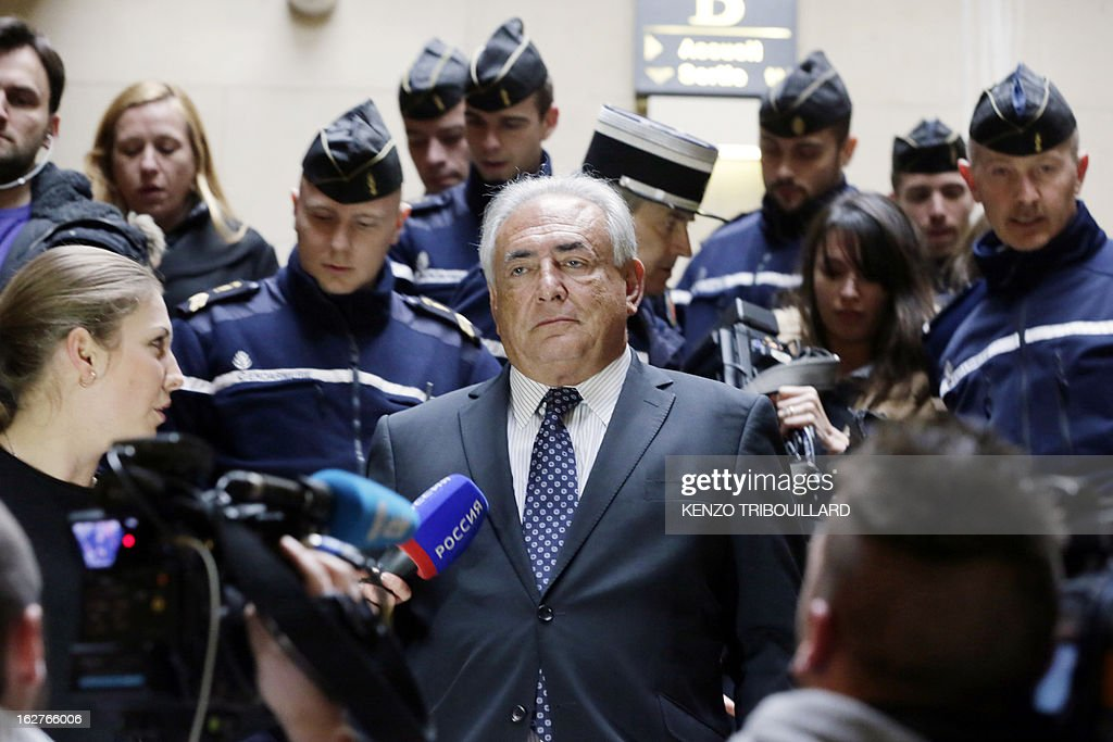 Disgraced former IMF chief Dominique Strauss-Kahn (C) leaves Paris' courthouse after attending a hearing regarding his seizure request of the new book by Argentinian-born Marcela Iacub detailing their liaison, on February 26, 2013. Strauss-Kahn, who has called the book an 'abomination', is seeking 100,000 euros ($132,300) in damages and compensation from Iacub and her publisher Stock, and a similar amount from Le Nouvel Observateur, a magazine that published excerpts of the book.