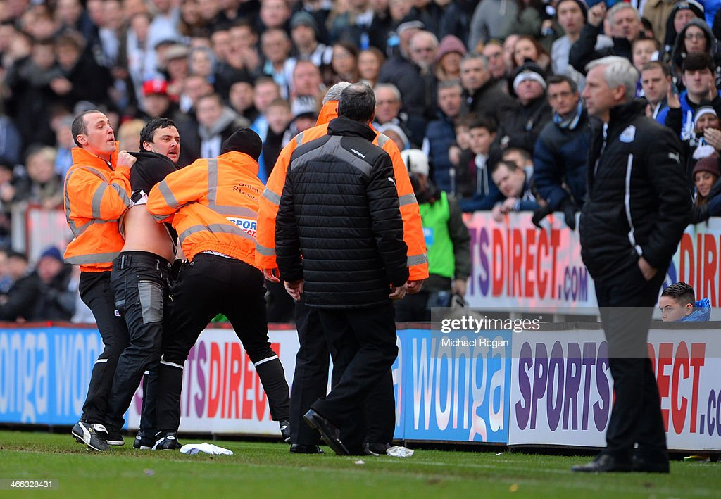 A disgruntled Newcastle fan shouts at <a gi-track='captionPersonalityLinkClicked' href=/galleries/search?phrase=Alan+Pardew&family=editorial&specificpeople=171147 ng-click='$event.stopPropagation()'>Alan Pardew</a> the Newcastle manager as he is removed from the pitch by stewards during the Barclays Premier League match between Newcastle United and Sunderland at St James' Park on February 1, 2014 in Newcastle upon Tyne, England.