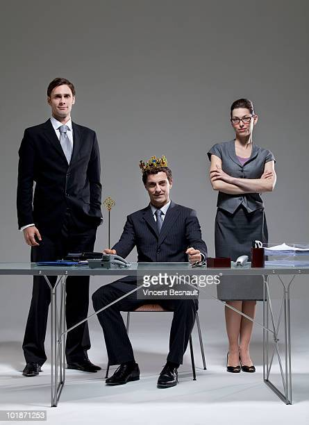 CEO disguised as a king with two employees