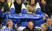 Disguised as smurfs supporters of the Moulins football club cheer before the start of a French Cup quarter final football match between Moulins and...
