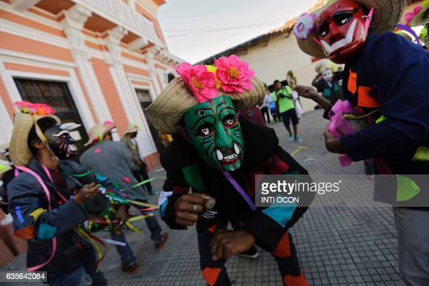 Disguised dancers take part in the XIII Poetry Festival in Granada some 45 kilometres from Managua on February 15 2017 Poets from America Asia Europe...