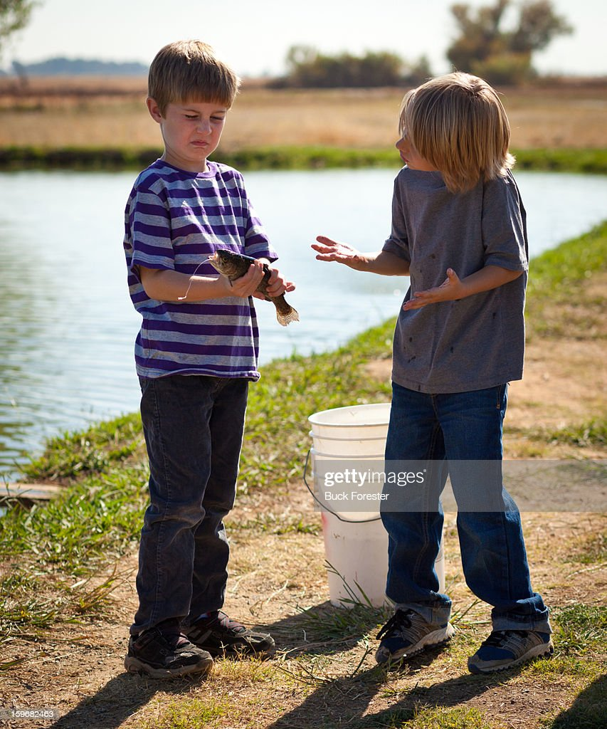 Disgusted Boy Holding Trout : Stock Photo