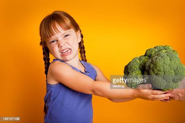 Langsam kleines Mädchen mit Brokkoli und Wincing