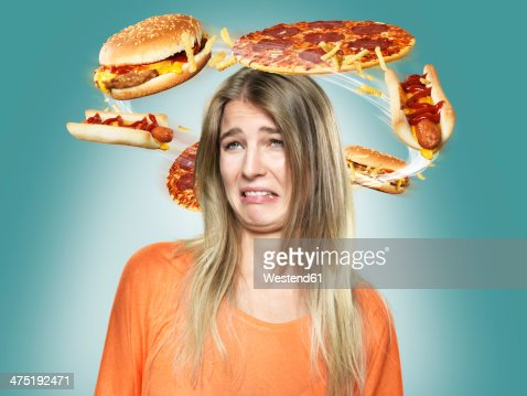 Disgusted young woman with flying fast food around her head, Composite