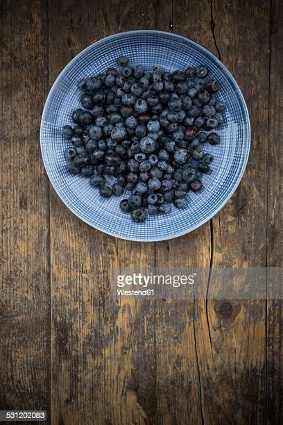 Dish of blueberries on wood