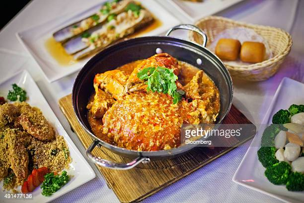 A dish of chili crab center sits among other dishes on a table at the Jumbo Seafood Riverside restaurant operated by Jumbo Group at Clark Quay in...