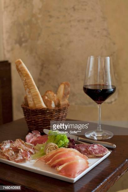 Dish of cold pork meats ,bread sticks and a glass of red wine on a table in a restaurant