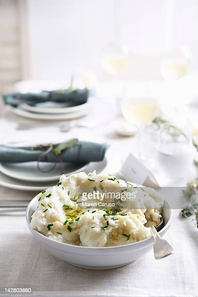 Dish of mashed potatoes with table settings