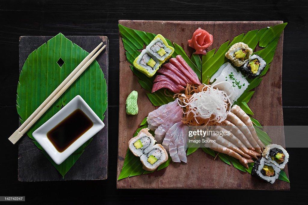 Dish of sashimi and sushi rolls