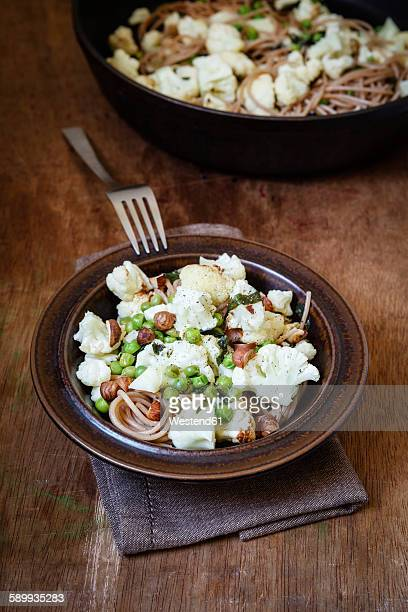 Dish of whole grain spelt spaghetti with roasted cauliflowers, hazelnuts, peas and basil
