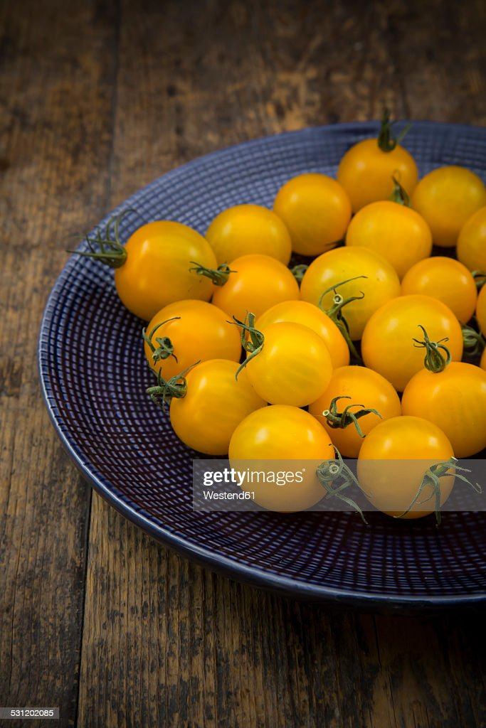 Dish of yellow cherry tomatoes on dark wood, partial view