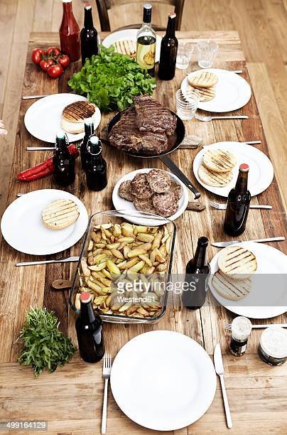 Dish with potatoes, steaks and meatballs on wooden table