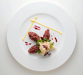 Dish with quenelle of red rice, fish tempura and sprouts top view