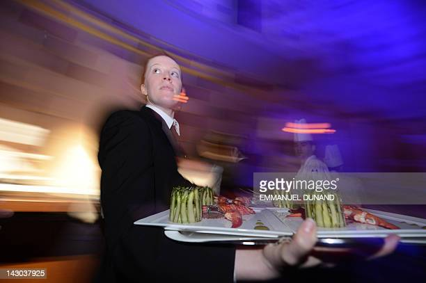 Dishes are brought to the tables during the 'Relais Chateaux 2012 Grands Chefs Dinner' at Gotham Hall in New York April 16 2012 Fortyfive chefs from...