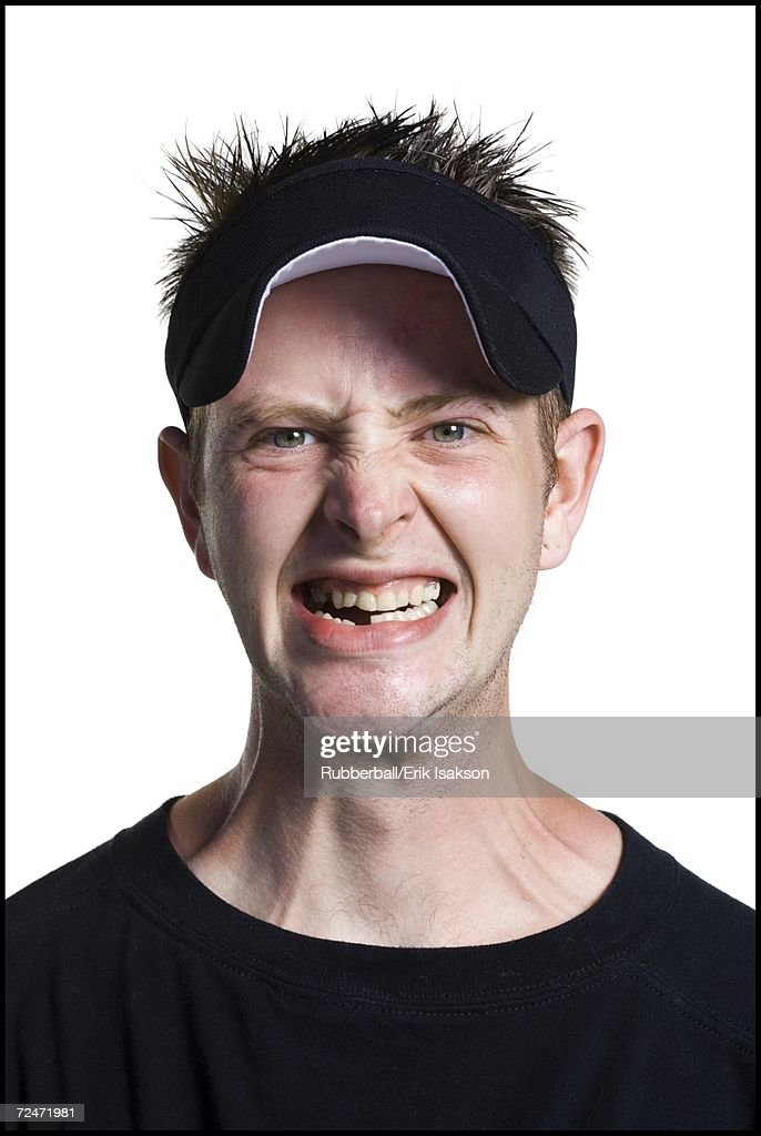Disheveled man with a visor grinning
