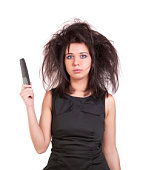 Disheveled woman with the long, black hair, in a black dress holding a comb. Isolated on white.