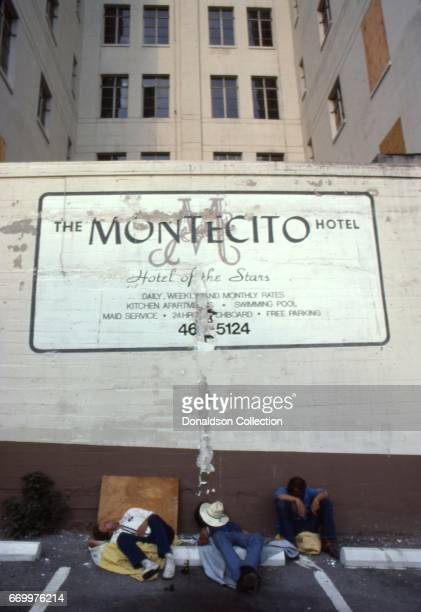 3 dishevelled possibly drunk transient men sleep during the daytime in a parking lot of the Montecito Hotel with a sign that reads 'The Montecito...