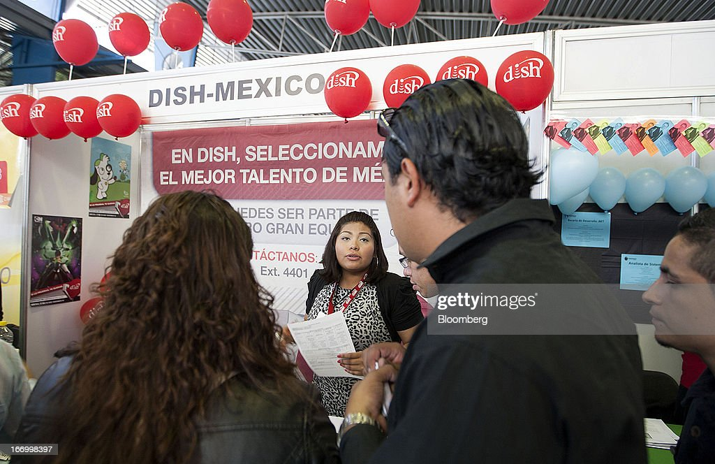 A Dish-Mexico representative speaks with job seekers during the XXVII job fair at the Palacio de los Deportes in Mexico City, Mexico, on Thursday, April 18, 2013. Mexico created 53,994 permanent and temporary urban jobs in March, according to reports from the Mexican Social Security Institute (IMSS). Photographer: Susana Gonzalez/Bloomberg via Getty Images