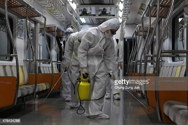 Disinfection workers wearing protective gears spray antiseptic solution in an subway amid rising public concerns over the spread of MERS virus at...
