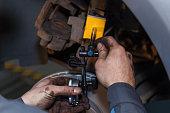 The man is repairing the disc brake machine, close-up. Disk brake repair in the car.