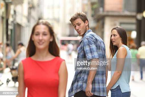 Disloyal man with his girlfriend looking at another girl : Stock Photo
